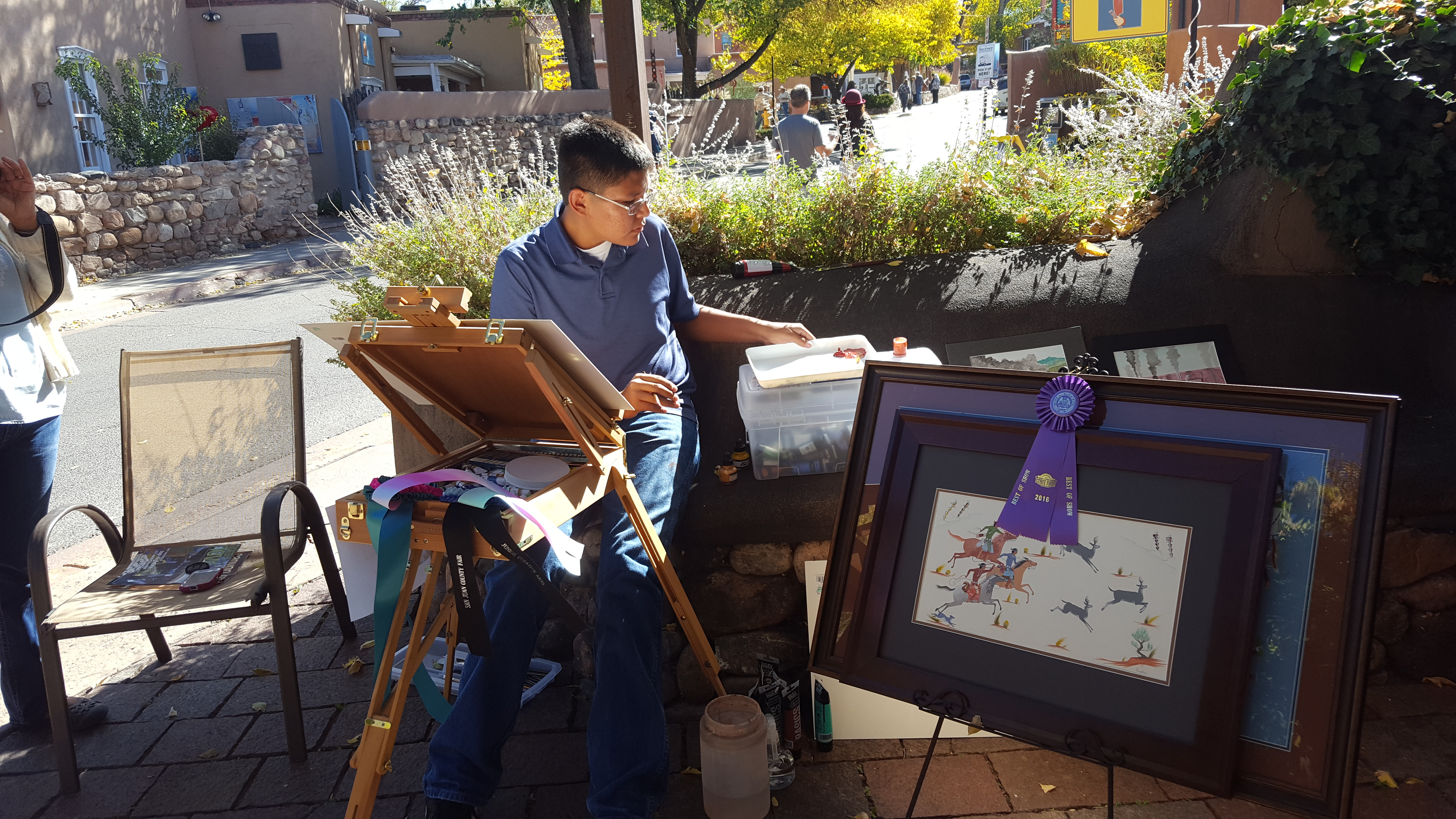 Myron Denetclaw (2000 - ) painting in front of Adobe Gallery during the Canyon Road Paint Out.