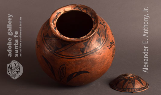 This rare and historic Tesuque Pueblo pottery vessel has an inner rim designed to support a lid. It was not unusual at Tesuque for the potters to make lidded jars. Most lids have been lost or broken. Fortunately, the lid for this jar is still here, missing only the knob.