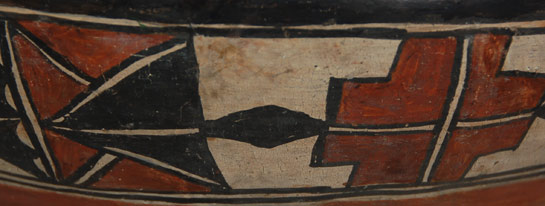 This is a turn-of-the-century polychrome bowl from San Ildefonso Pueblo that is totally slipped inside and outside with traditional Cochiti Pueblo rag-wiped white slip. The interior is decorated in a continuous chain of cloud forms, which are pendant from the lower of two parallel framing lines just below the rim.  The exterior design is an array of different elements. There are crosses, triangles, clouds, diamonds and kiva-step elements, all arranged in a two-inch-wide band encircling the upper body of the bowl. The design band is enclosed within framing lines above and below. A black rim and a wide red band under the painted area complete the design. There has been some professional conservation and restoration.     Provenance: This Polychrome Interior & Exterior Decorated Bowl was shown in the exhibit BOWLS: A Pueblo Necessity December 15, 2006 until December 31, 2006 presented at adobe gallery Santa fe.
