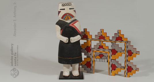 The tableta was made from crate wood, not plywood, another indication of the earlier age.  As is traditional, there are rain clouds and rain on her tableta and a rainbow on her chin.  She is wearing the traditional black manta with a shawl draped over her shoulders.  The tableta was made separately and slips into slots on the head of the doll.