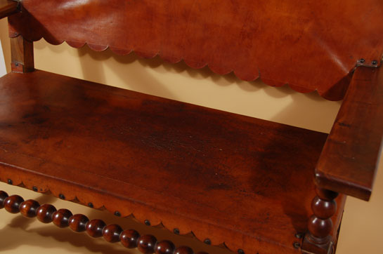 This is the style bench one would find in a Fred Harvey hotel such as The Alvarado in Albuquerque or La Posada in Winslow or any of the other many locations along the rail route from Chicago to California.  It is certainly of the Mission style with the saddle leather back and seat, both of which have curves on the ends of the leather.  There is no manufacturer's name on the item which leads even more to the likelihood that it was handmade for one of the hotels.  We have no documentation to substantiate this but it could be highly likely.  Condition:  the leather is worn in places and there is a 3-inch slit at the front left seat.  The seat is still useable.  Provenance:  from the Albuquerque residence of Alexander E. Anthony, Jr. where it was used in the front entryway from 1985 until the move to Santa Fe in 2005.  It has been in storage since 2005.