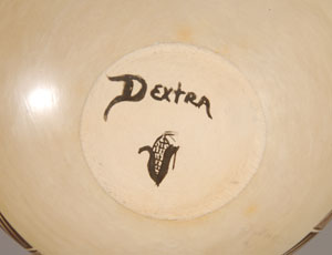 Dextra descends from a distinguished ancestral line of potters—beginning with the Sikyatki ancestors of prehistoric times and more recently from her great-grandmother, Nampeyo of Hano and her grandmother Annie Healing Nampeyo. Following tradition in every aspect of construction and firing has always been a rule with her, but using her own creative talent in the execution of vessel shape and design is what has set her apart from others and made her one of the greatest Hopi potters of the 20th Century. She was born on September 6, 1928 on the Hopi Reservation where she still maintains her home.