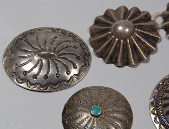 This group of seven silver buttons and concha came from the Balcomb family that owned a gallery in Gallup, New Mexico, and later in Albuquerque.  Mrs. Balcomb retired and closed the Albuquerque gallery in 1976.  These buttons were most likely in the earlier gallery in Gallup, the heart of Navajo Indian country.  Three of the buttons are fluted and measure 1-3/8 inch in diameter each.  Two of the buttons are stamped and measure 1-9/16 inch in diameter each.  The single button with a turquoise cab is stamped and measures 1-1/4 inch in diameter.  The oval silver one is a concha with a copper strap on verso through which a leather belt could be threaded.  It measures 1-9/16 inch x 1-3/4 inch.  Condition:  all are in original condition  Provenance:  from the Balcomb family