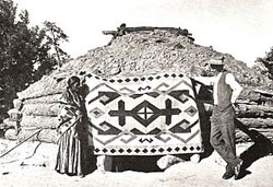 J.B. Moore with a weaver and rug at the Crystal Trading Post, from the 1911 catalog - Image Source: Wikipedia