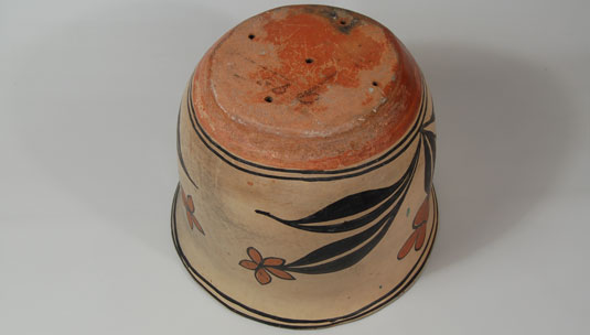 The shape of the vessel suggests that it was made for use as a flowerpot. Five holes drilled in the bottom further substantiate this thought.