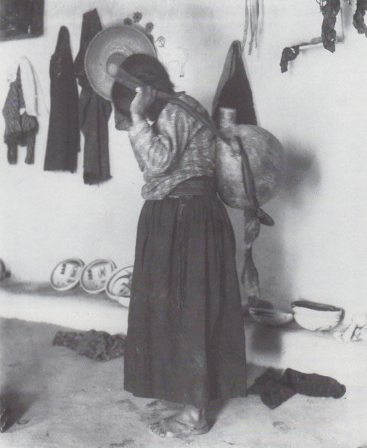 """Nampeyo carrying an olla/"" Adam Clark Vroman, 1901.  (The Southwest Museum, Los Angeles.  Photo #N22764.)  Nampeyo posed for Vroman inside her home with a typical canteen carried by women to carry water from the spring below the mesa.  Photo part of public domain."