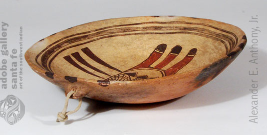 This Polacca Polychrome bowl is most certainly one made in the 1890s as an item intended for sale.  It has a lug on the back side from which it can be hung on a wall, something for which a Hopi would have no use.  The design features elements of rain, rain clouds, and tail feathers.