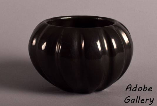 Alternate view of this ribbed black polished pottery vessel.