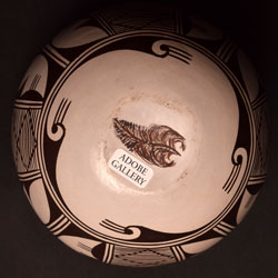 This rich brown-on-white small storage jar by Helen Naha, Feather Woman is signed on the bottom with her hallmark feather glyph.