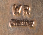 The choler is stamped with the initials WR and Sterling.  None of our reference books lists a silversmith with those initials so we have been unable to state the name of the jeweler of this exquisite jewel of choker.