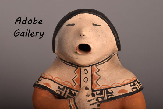 Close up view of the face of this storyteller figurine.