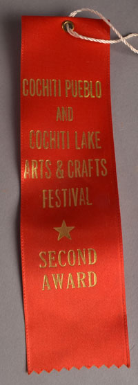 This figurine was entered in competition at the Cochiti Pueblo and Cochiti Lake Arts & Crafts Festival in October 1981 and was awarded a Second Award ribbon.