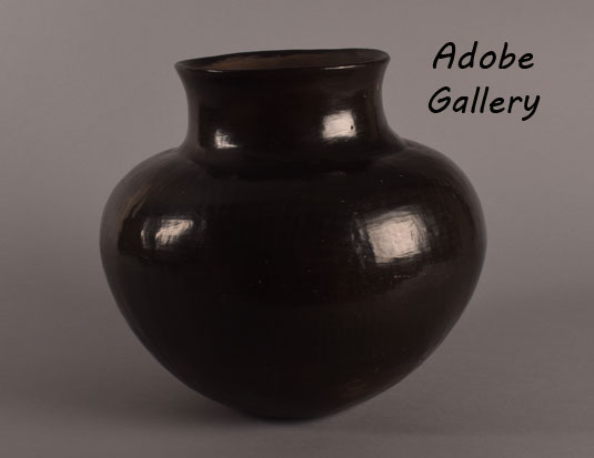 Alternate view of this jar.  When this San Juan Pueblo historic pottery jar was in the formative stages, with coils of clay being stacked row upon row, and the clay was still moist, it is likely that the weight of the jar as it got taller, resulted in a tilt to one side.  This is not an uncommon occurrence.