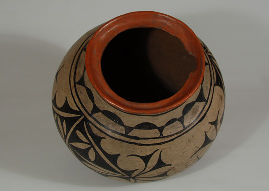 This jar has all the attributes of San Ildefonso Polychrome.  The traditional San Ildefonso slip was used, as evidenced by stone-polishing marks.  A red rim extends down into the interior lip, a lip that features an opening to accommodate the handle of a ladle.  There probably was a lid for the jar at some point but it no longer exists.