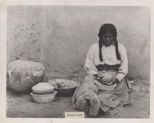 This potter was staged by an unknown photographer at an unknown date.  The potter is identified as Tewingyinema.  We are appreciative to Hopi-Tewa potter, Mark Tahbo, for sharing this photograph with us.  The photograph was recently found in a burned out home at First Mesa.